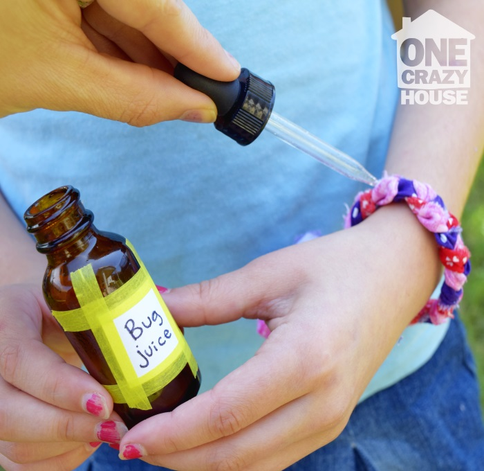 girl with bracelet on her wrist and mom adding drops of mosquito repellent to the bracelet