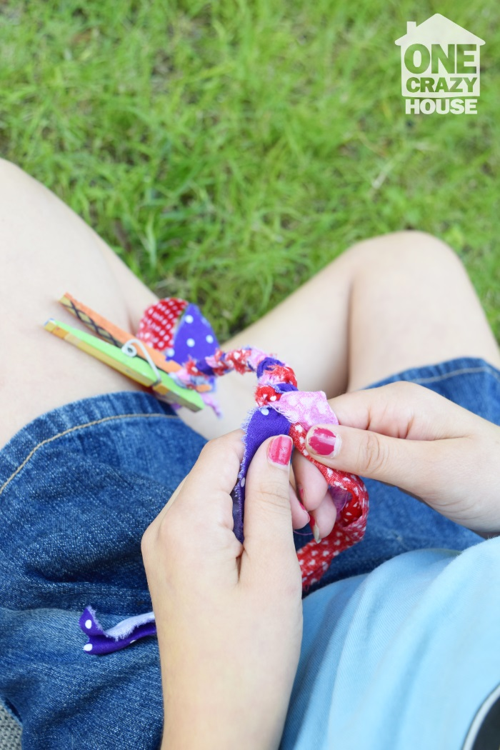 girl sitting in the grass braiding fabric pieces together