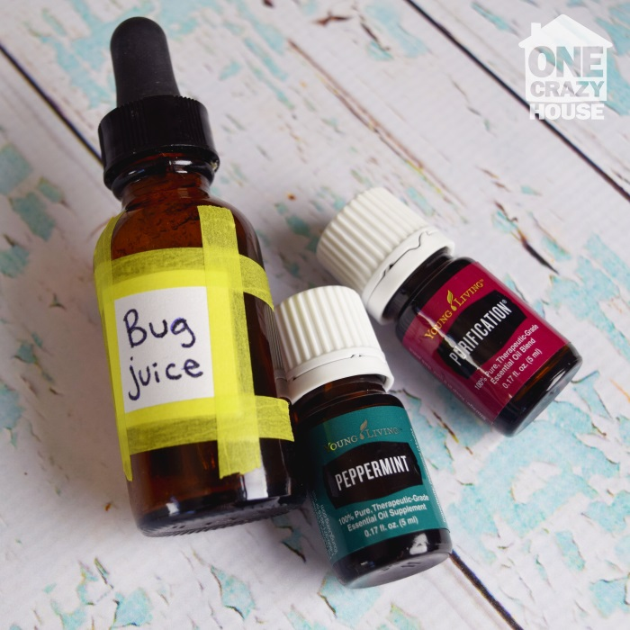 "essential oils and dropper bottle with ""bug juice"" label lying on a table"