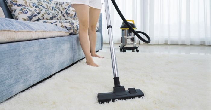 woman vacuuming carpet as part of the spring cleaning list