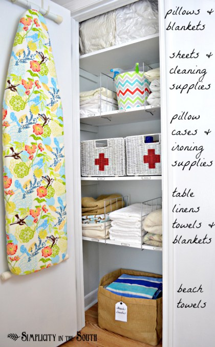 linen closet organization includes ironing board, bins, baskets and floor basket for towels