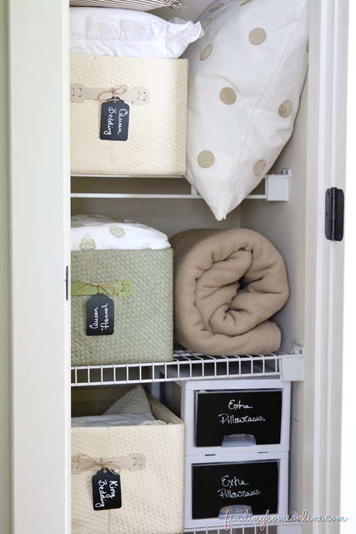 linen closet ideas - shelves clean with bins holding linens, blankets and pillows