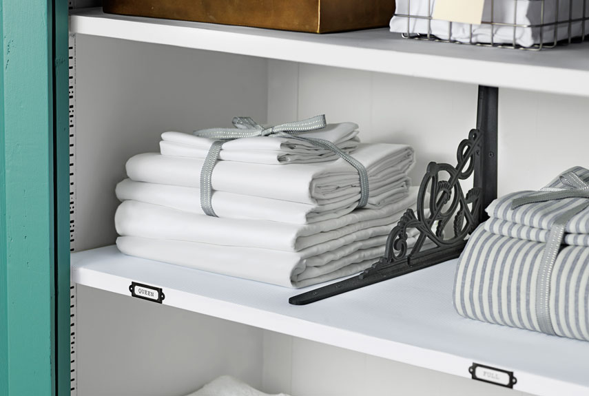 shelves are organized with stacks of linen neatly between decorative dividers