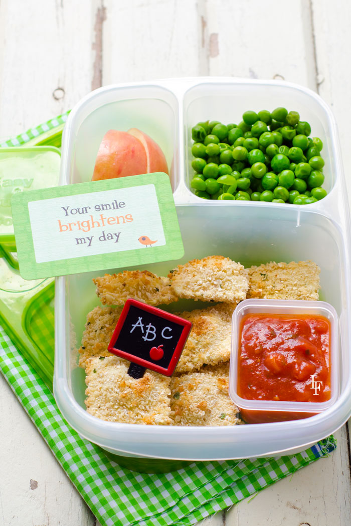 school lunch ideas bento box with baked ravioli, peas, apple slices and a sweet note.
