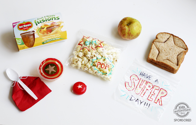 super hero themed lunch with sandwich, apple, popcorn and fruit