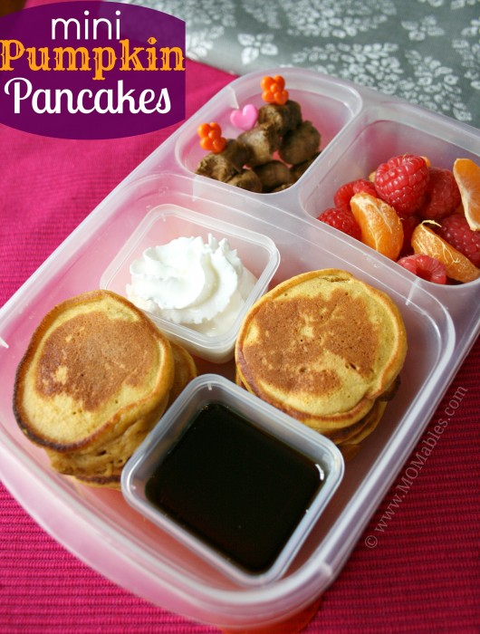 pumpkin pancakes in a bento box with fruit, meat and syrup.