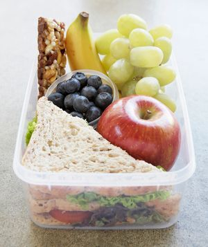 healthy school lunch idea of sandwich, apple, grapes, blueberries, banana and nut bar