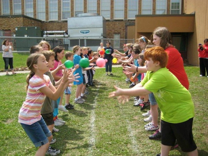 two lines of children in the grass playing water balloon toss