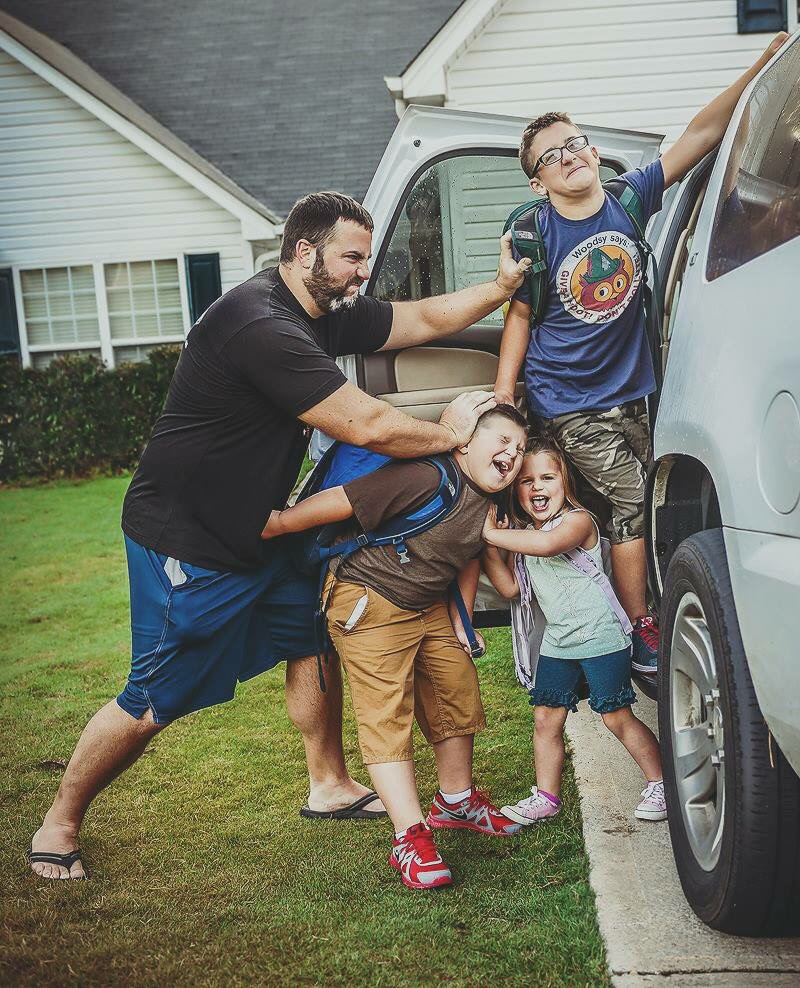 dad pushing kids into car on first day of school