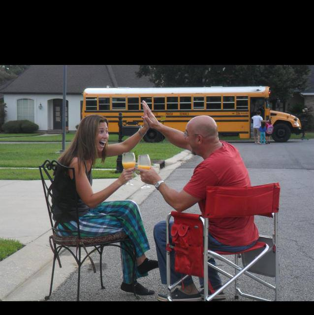 parents celebrating with high fives and drinks as kids get on the school bus