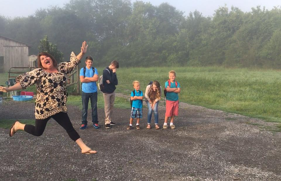 mom jumping for joy while her kids stand in the background on the first day of school