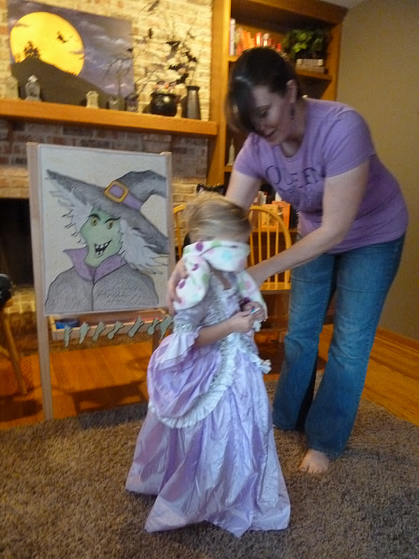 kid playing pin the nose on the witch