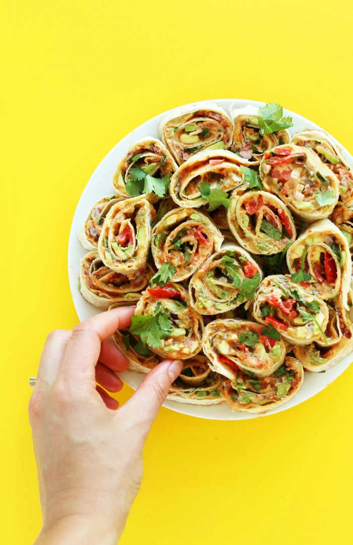 hand grabbing 6-layer Mexican easy pinwheels on a plate