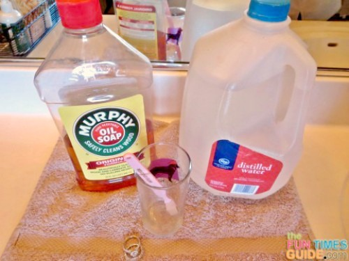 A bottle of Murphy's Oils Soap with a gallon jug of distilled water and a glass with a toothbrush