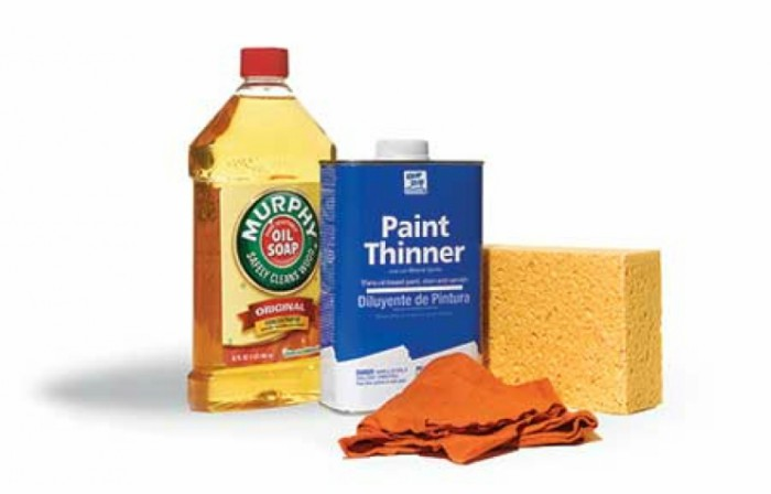 A bottle of Murphy's Oils Soap with can of paint thinner, a sponge and a rag
