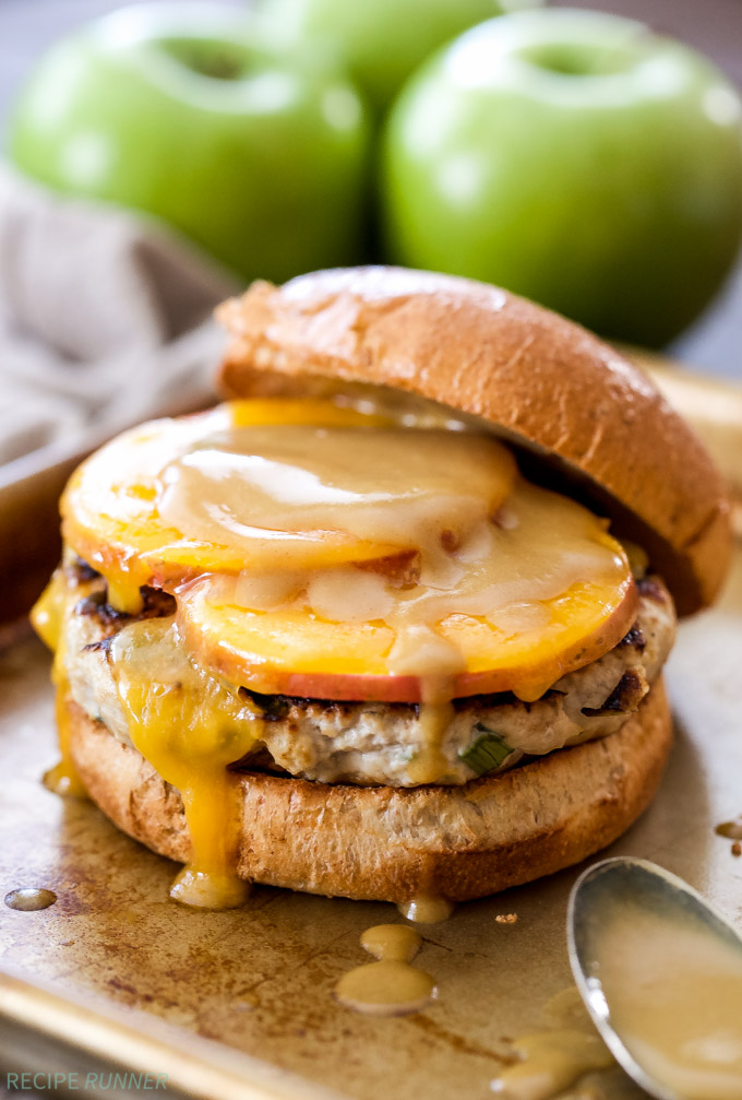 Apple cheddar turkey burger with top bun sliding off and apples in the background