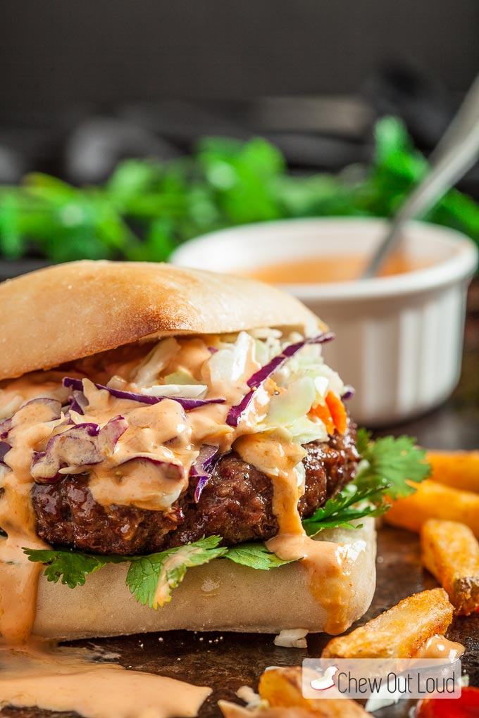 close up of Asian burger with sriracha mayo and cole slaw