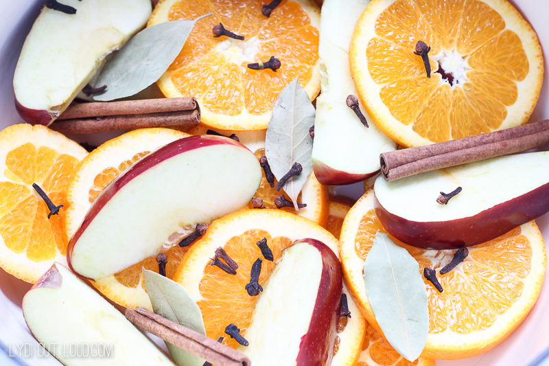 pan filled with orange and apple slices, cinnamon sticks, cloves and bay leaves