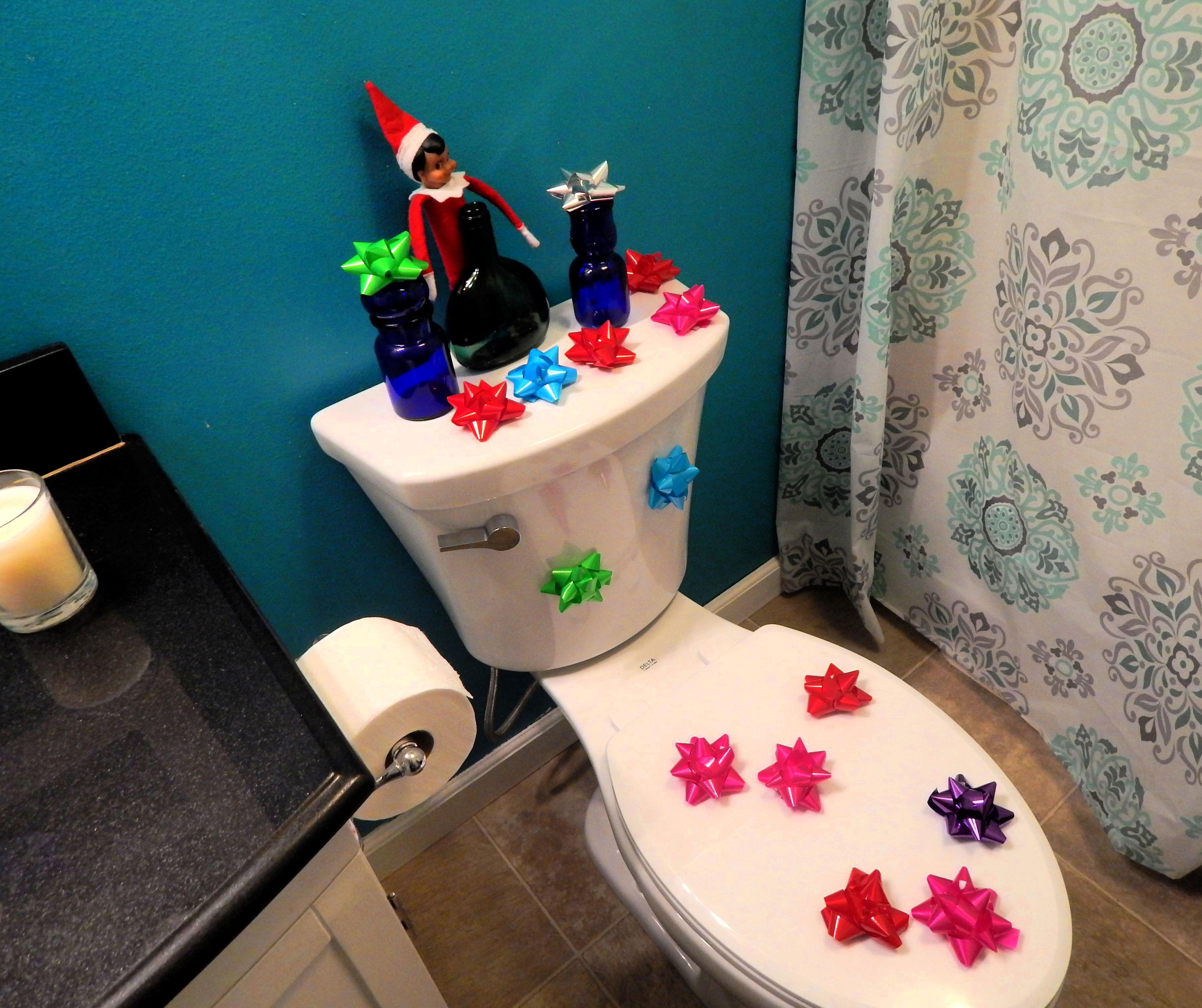 toilet with christmas bows stuck to it