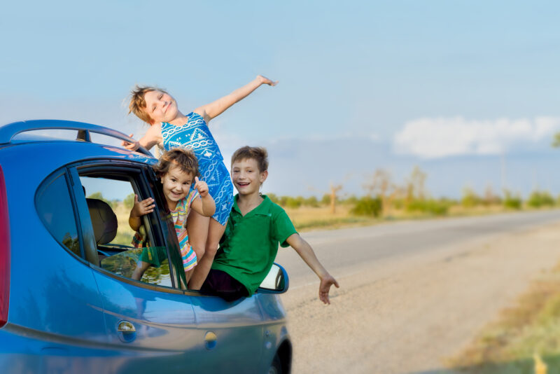 3 happy kids leaning out of a car while parked on the side of the road during a spring break road trip