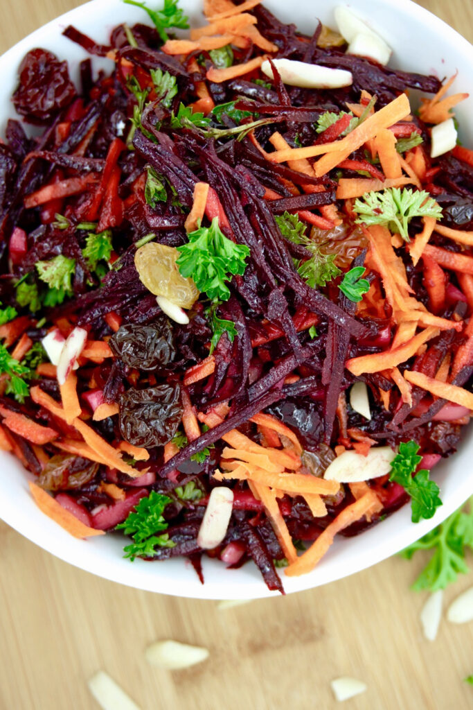 Beet carrot raw slaw with a tossed dressing in a white bowl.