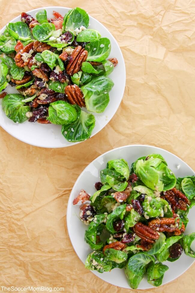 White plates with brussels sprouts, walnuts, dried berries and walnuts.