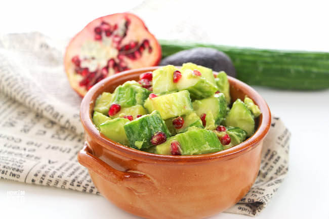 Brown bowl filled with cubes of avocado, cucumber and pomegranate seeds.