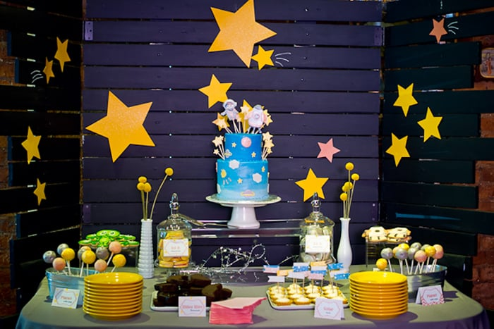 wood slat painted dark blue with yellow stars behind a table full of baby shower desserts