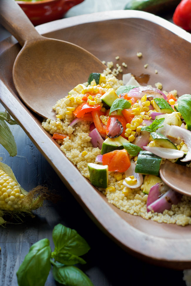 Wooden bowl with quinoa, corn, cucumbers, tomatoes, onions and other summer vegetables.