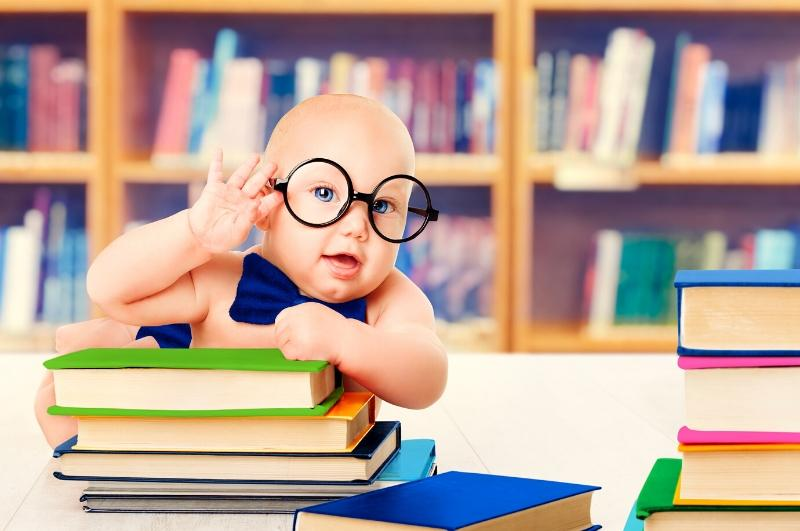 Baby with large glasses and a bow tie propped up over a stack of books