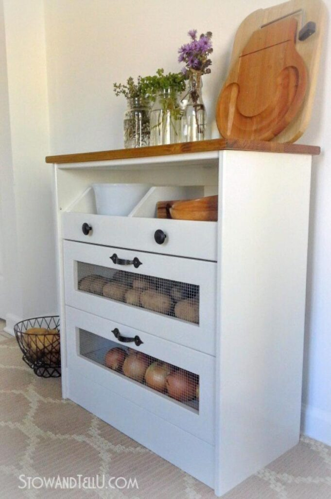 white vegetable bin with drawers and stained wood top