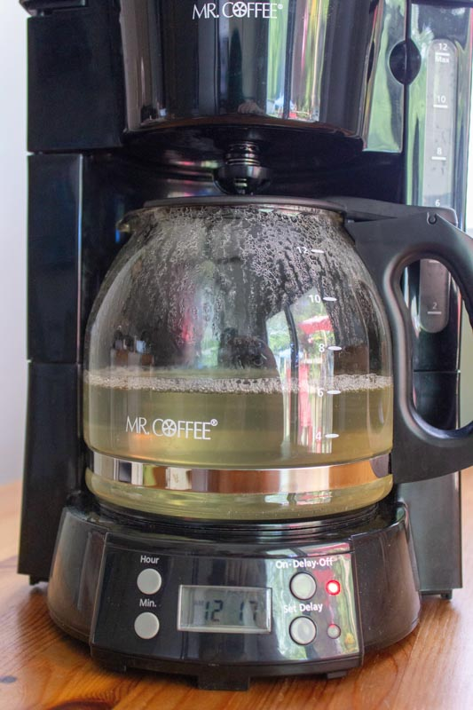 Coffee maker with vinegar being cleaned