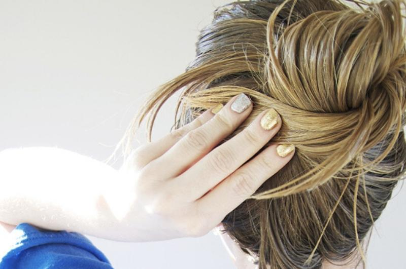 woman tying her long hair into a bun