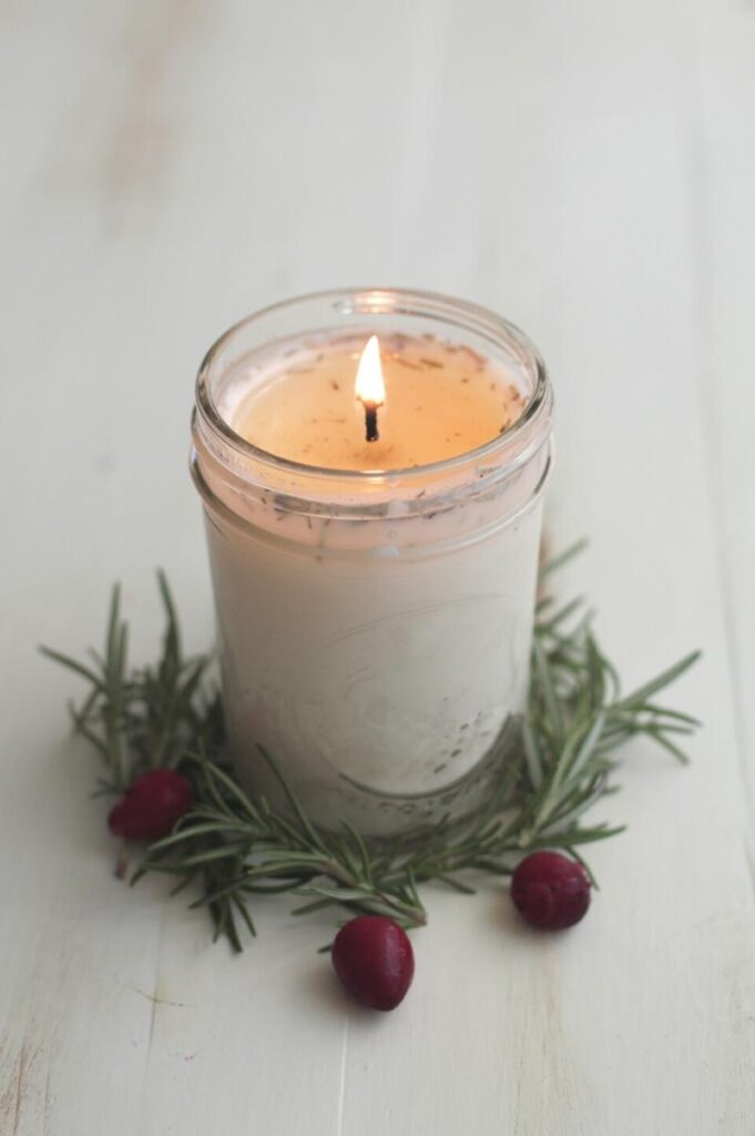 DIY candle with a lit flame and a wreath of greenery around the base of the jar