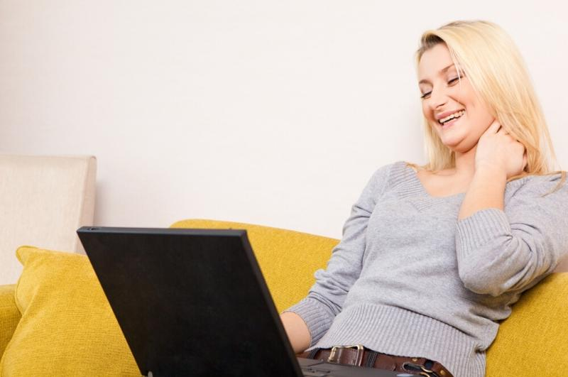 woman sitting on couch with her laptop laughing as a mood booster