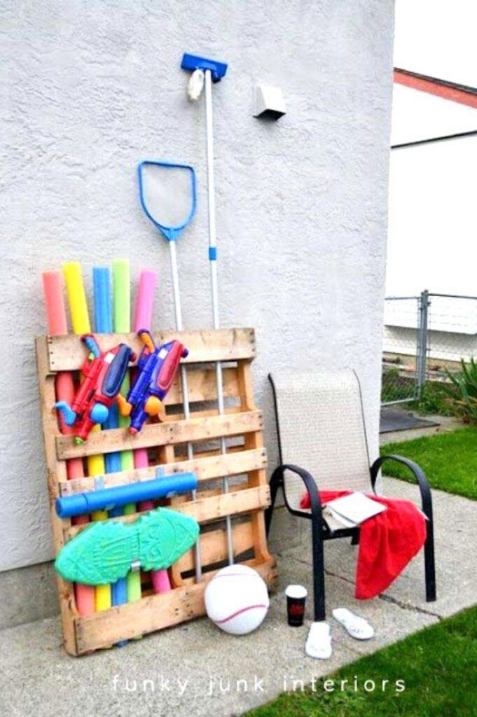 wood pallet leaning against a wall storing pool toys and supplies