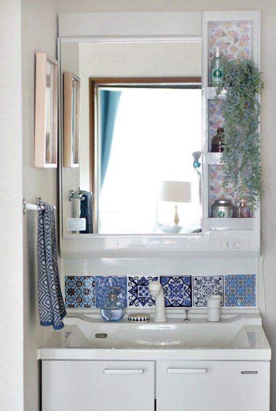 white bathroom with blue patterned tiles for a backsplash