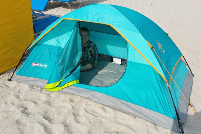 tent set up on a beach with the flap open and a child inside