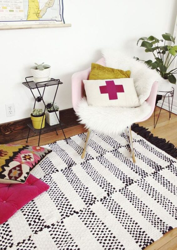 apartment room with a throw rug on the floor and throw pillows on a chair