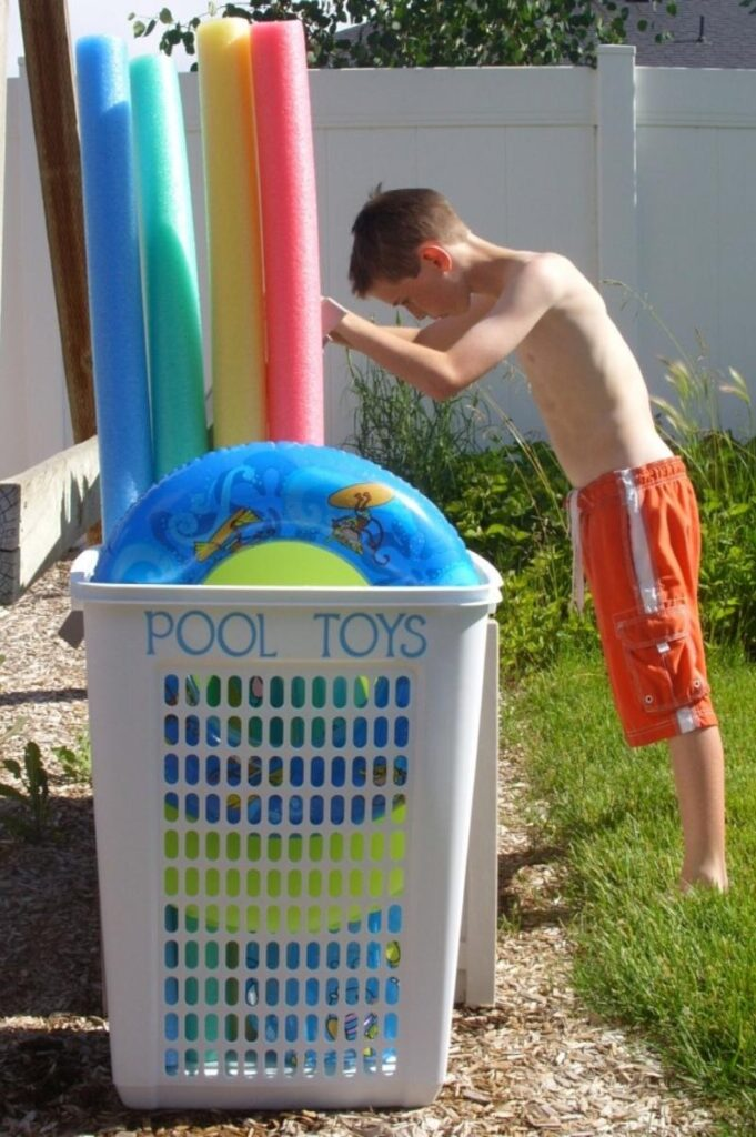 child looking through laundry hamper holding pool noodles and pool toys