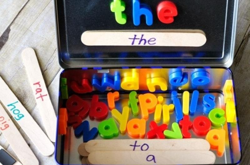 metal lunchbox with magnetic letters and popsicle sticks with words written on them