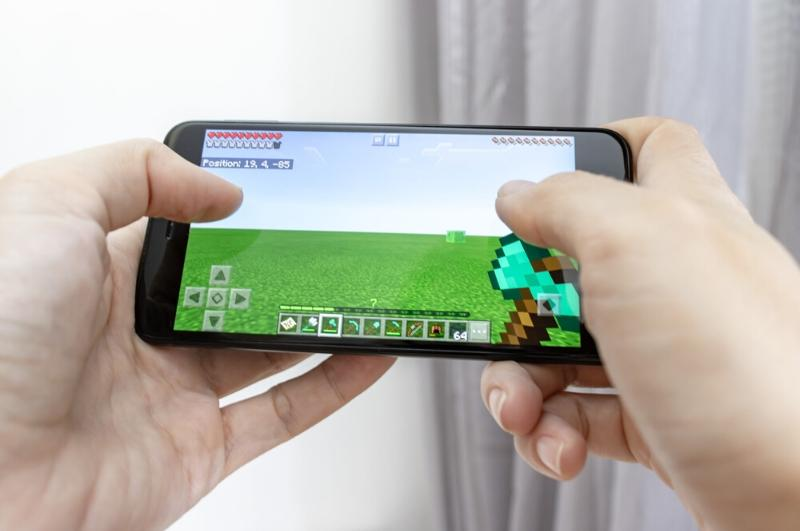 kids hands holding phone and playing Minecraft