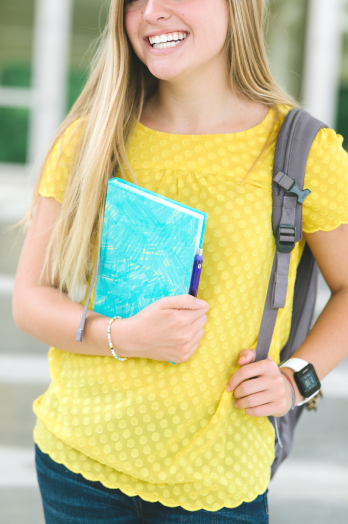 Girl smiling and holding a full focus student planner