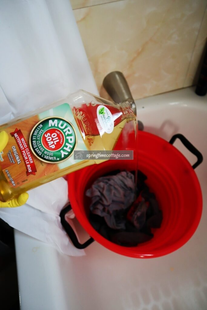 Pouring Murphy's Oils Soap into a bucket of clothes