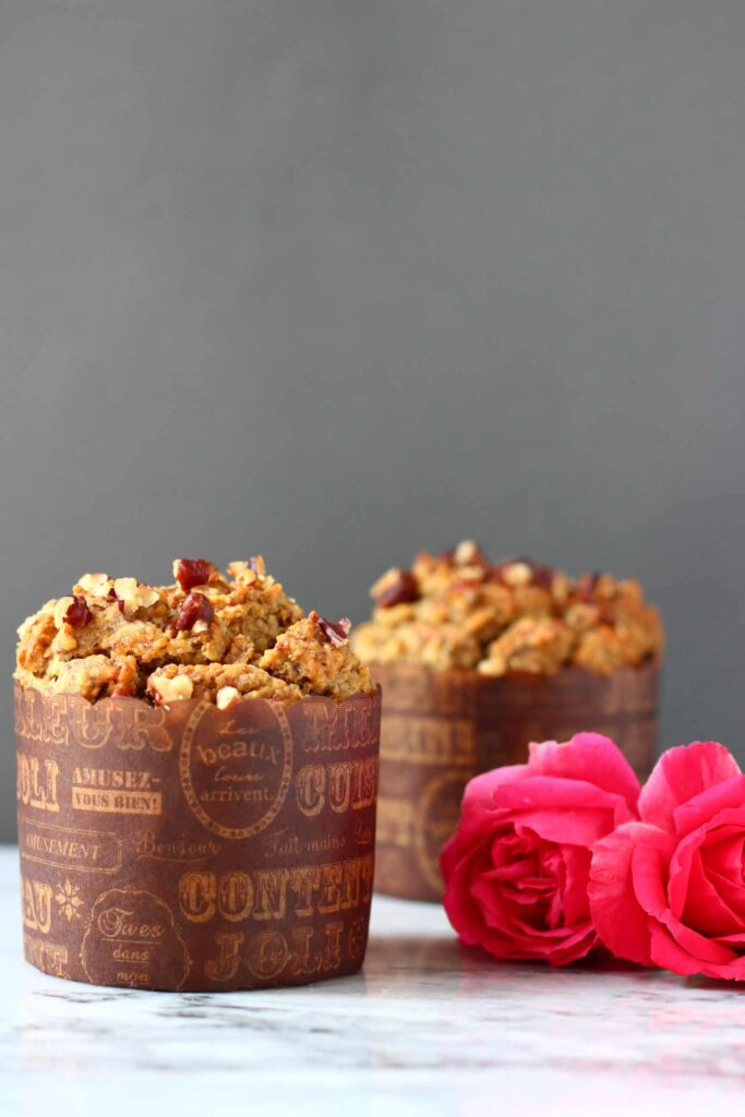 vegan pumpkin muffins on a counter with pink roses