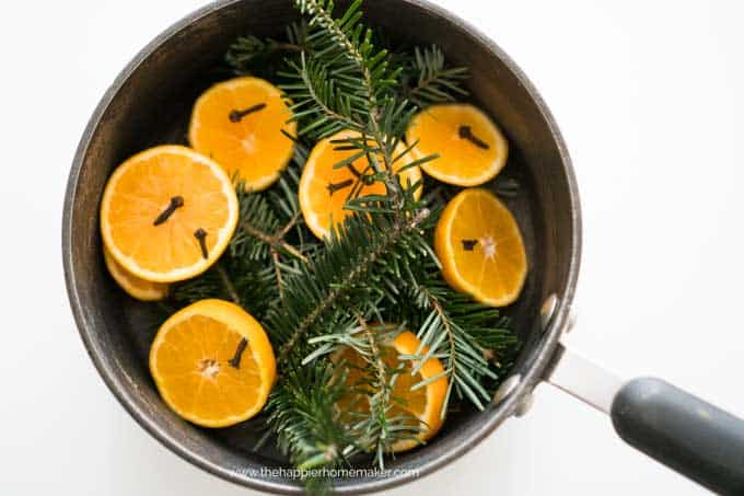 pan with cloves, orange slices, and evergreen branches