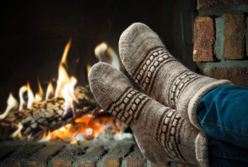 feet in heavy winter socks in front of a fire