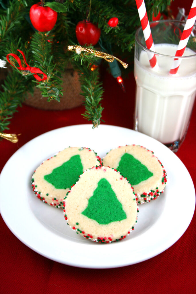 Slice and bake Christmas cookies on a plate with a glass of milk.