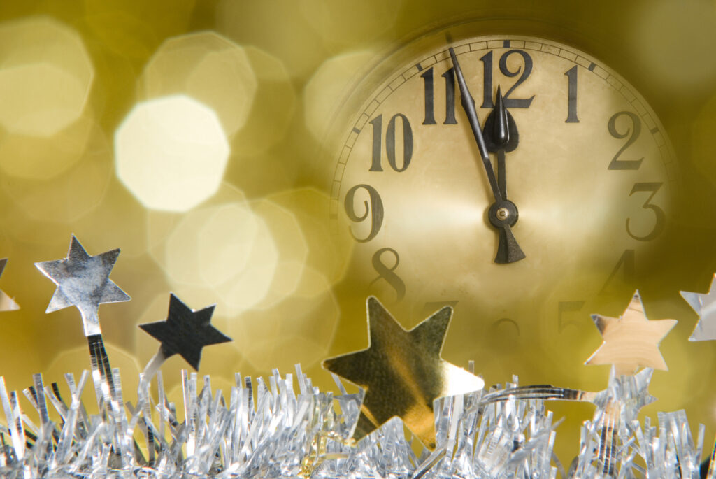 clock near midnight and party streamers