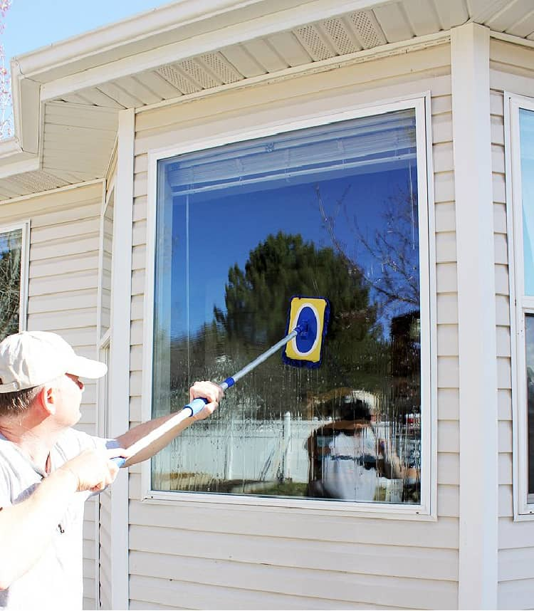 Man cleaning the outside windows with a long-handled brush